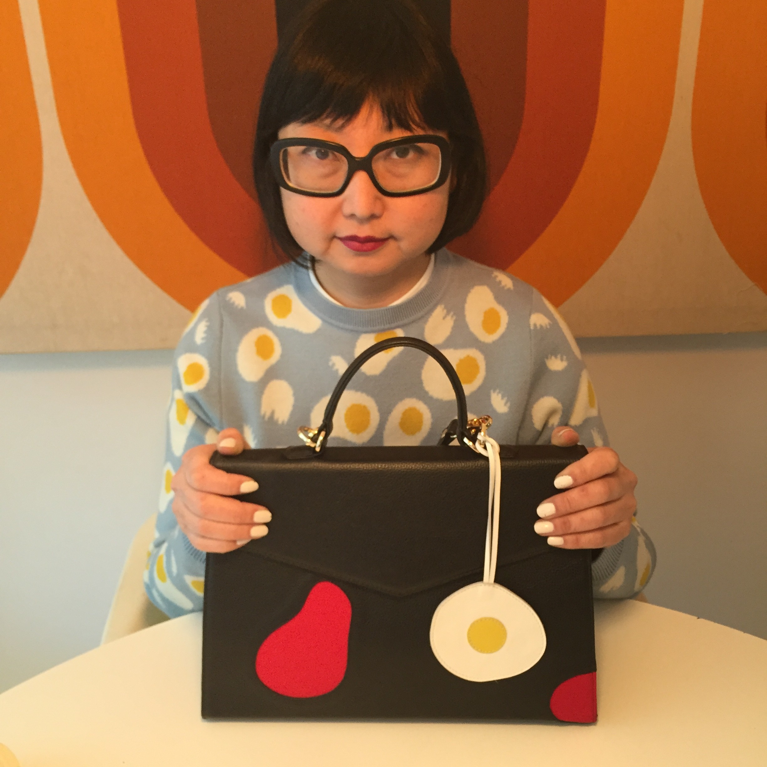 I love the charms that you can get to put on your bag.  I like to match my outfit with the charm, like this egg charm which matches my Lazzari sweater designed by Olimpia Zagnoli whose graphic design work I really admire.