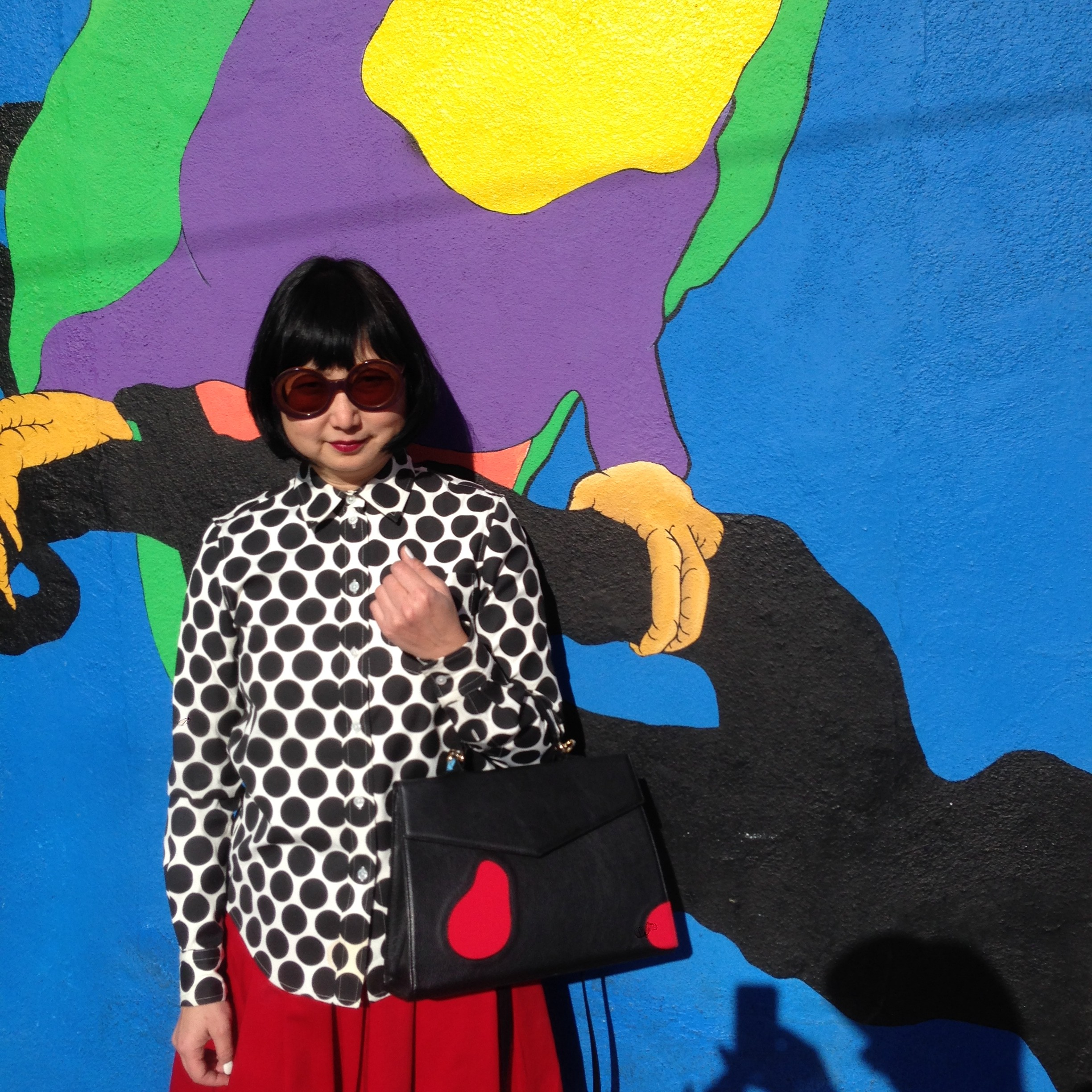 Next door to Tacos Villa Corona is a bird shop with parrots in the window.  This is their colorful parrot mural.  This is the outfit Alexander picked out for me.  He's partial to black and white I notice, but I love how he tied in the red in the skirt to go with the red of my bag.  It's helpful to get cats from an art gallery— they seem to have a good eye for color.